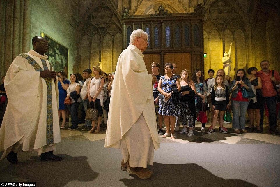 Sacerdotes Edgar Deguenon (esquerda) e Brice de Malherbe (centro) chegam para uma missa na catedral de Notre Dame em 26 de julho de 2016, em Paris, em memória do sacerdote assassinado na cidade de Normandy de Saint-Etienne-du-Rouvray