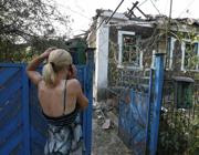 Una donna osserva la sua casa distrutta dai bombardamenti a Donetsk (Reuters)