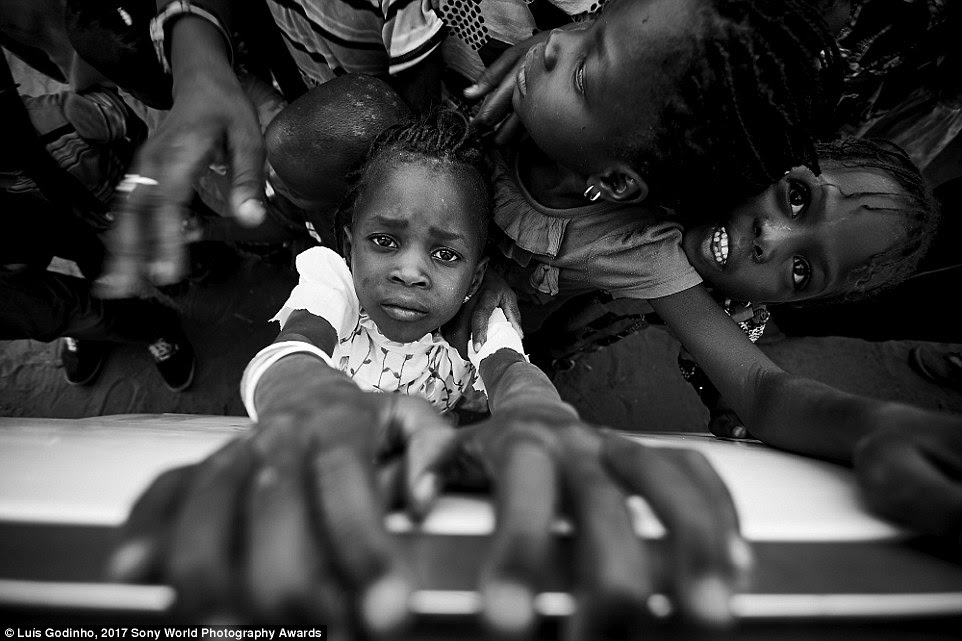 In Senegal, a young girl clings to the edge of a bus window with a strained expression on her face as the photographer shoots from above
