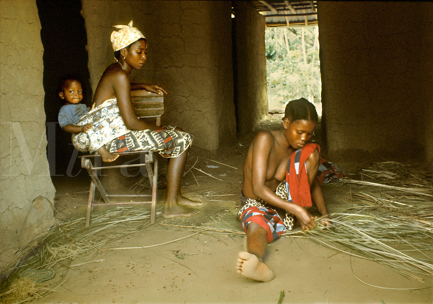 Women Of Kpelle Tribe Socializing Inside Hut Young One At Right Weaving Mat Woman At Left Carrying Baby Strapped On Her Back Liberia West Africa