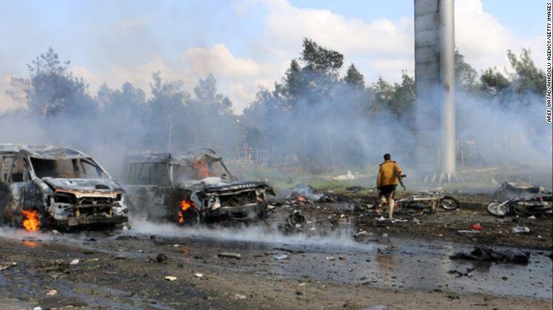Workers try to put out a fire at the site of Saturday's bombing of an evacuee convoy in Rashidin, Syria.