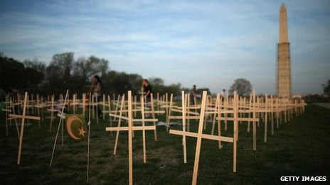 Volunteers place grave markers on the National Mall in Washington DC as over 3,300 crosses, stars of David, and other religious symbols are placed to remember those affected by gun violence 11 April 2013