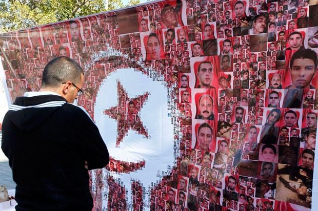 Homem observa homenagem durante a celebração do segundo aniversário da revolução tunisiana em foto de janeiro de 2013 (Foto: Anis Mili/Reuters)