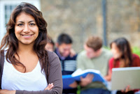 Student smiling with other students studying in background