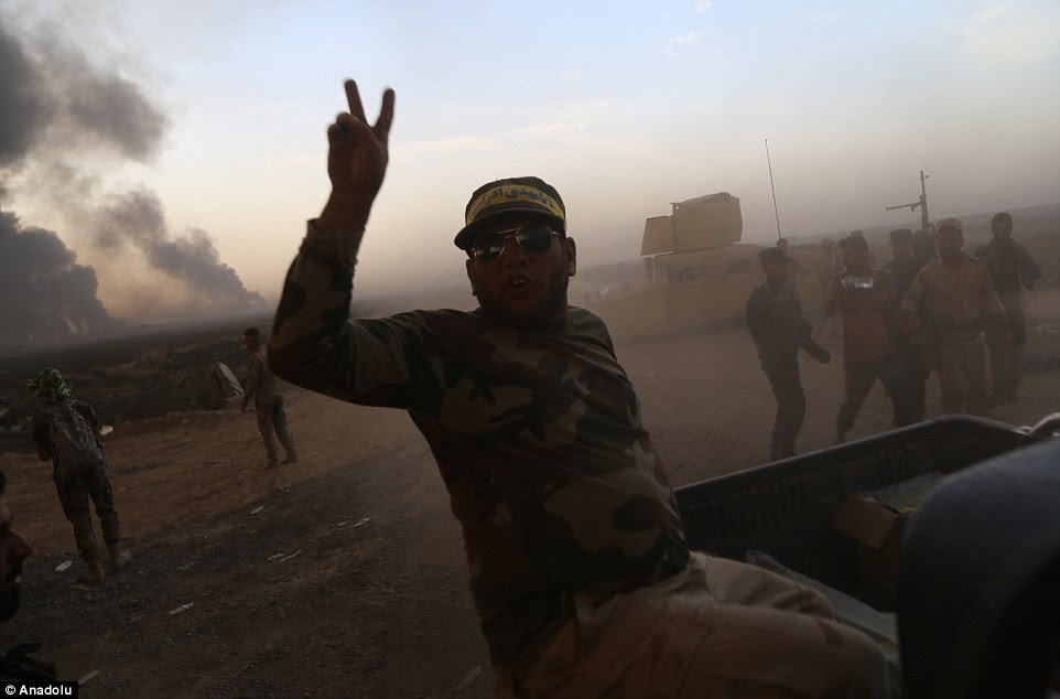 Iraqi army forces arrive in the village of Hut  as smoke can be seen rising from oil wells behind them