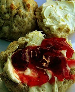 Clotted cream on scones with jam, also called Cream Tea. Note the little buttery clots on the yellow cream