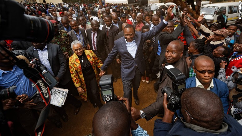 Kenya's President Uhuru Kenyatta high-fives with supporters after casting his vote in Tuesday's presidential election.