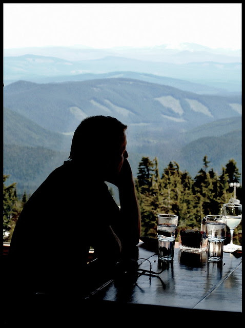 a guest looks out over the Cascade Mountain range from the Ram's Head Bar, third floor of the Timberline Lodge