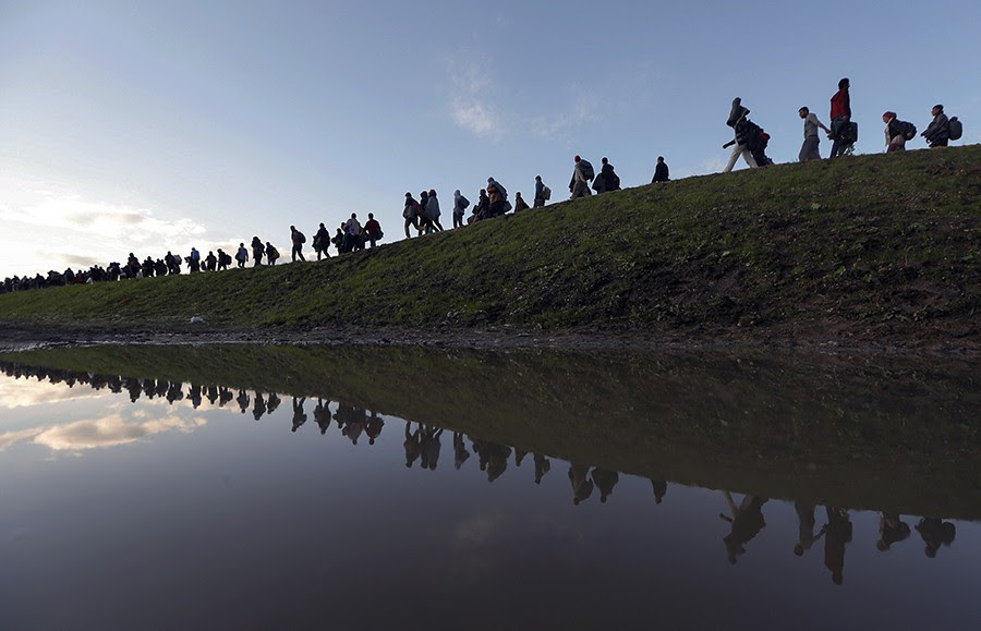 Migrants make their way on foot on the outskirts of Brezice, Slovenia. Slovenia's interior ministry raised the possibility on Tuesday of setting up physical barriers along its southeastern border if the numbers of migrants increased (Srdjan Zivulovic, Thomson Reuters - October 20, 2015).