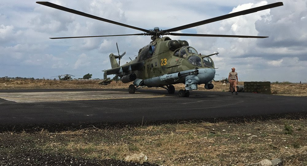 Ground crew servicing a Russian Mi-24 helicopter in Syria's Hmeymim airbase.