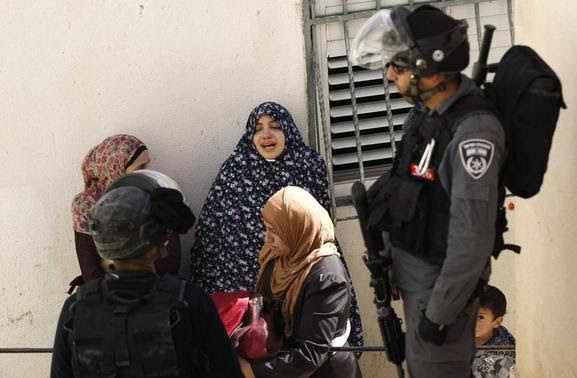 An Israeli policeman stands near Palestinian residents as they react after their home was demolished in Jabel Mukaber, a village in the suburbs of East Jerusalem February 5, 2014. REUTERS-Ammar Awad