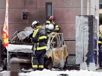 Firefighters investigate a burnt car at the site of an explosion in Utsunomiya, Japan. Pic: Kyodo/via Reuters
