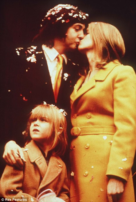 Inseparable: Paul McCartney and first wife Linda kiss on their wedding day in 1969 with Linda's daughter, Heather