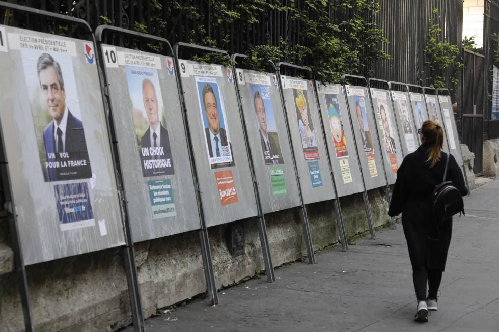 Una mujer pasa delante de los carteles de los candidatos de las elecciones presidenciales francesas en París.