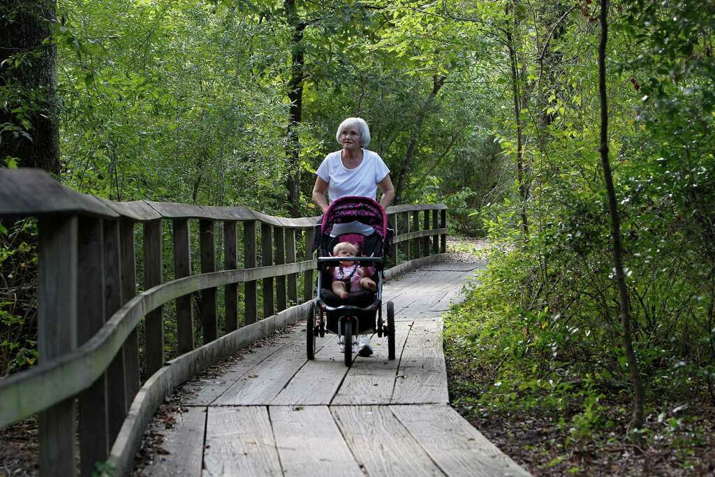 "Glenna Herron pushes her granddaughter, Ella Heron, 9 months-old, along a trail at the Houston  Arboretum & Nature Center. The Houston Arboretum & Nature Center's master plan and capital campaign for new facilities, wildscapes and paths,  will dramatically improve ""the silent giant"" that accounts for 10 percent of Memorial Park at its western edge.    ( Steve Gonzales / Houston Chronicle ) Photo: Steve Gonzales, Staff / © 2015 Houston Chronicle"
