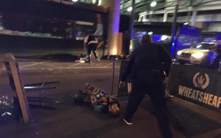 A picture taken in the Borough Market area showsa man lying on the ground who appears to have canisters strapped to him.
