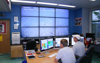 Photo of oceanographers watching the live video feed onshore at Rutgers University.