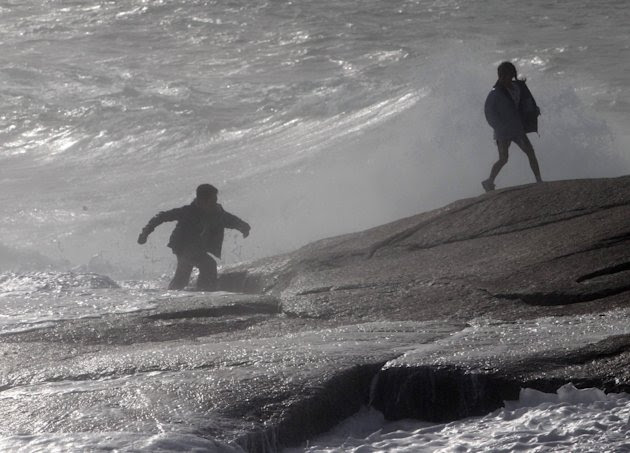 A man and his daughter scramble across the shoreline rocks after being hit by a wave on Sunday, Aug. 28, 2011 in Peggy's Cove, Nova Scotia. Atlantic Canada is experiencing increased wind and rain as t