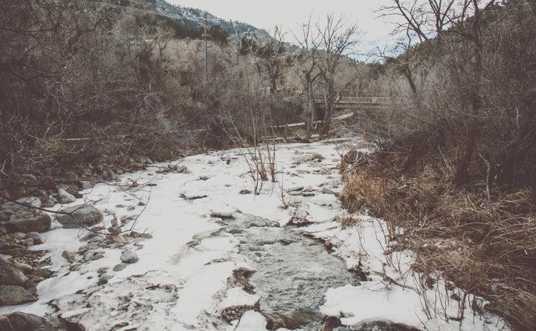 Photo of frozen boulder creek in winter
