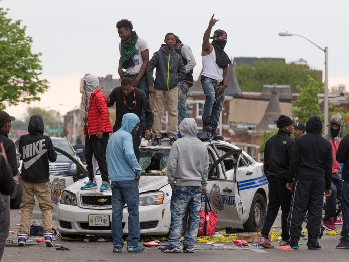Protesters stand on a demolished police car in Baltimore.
