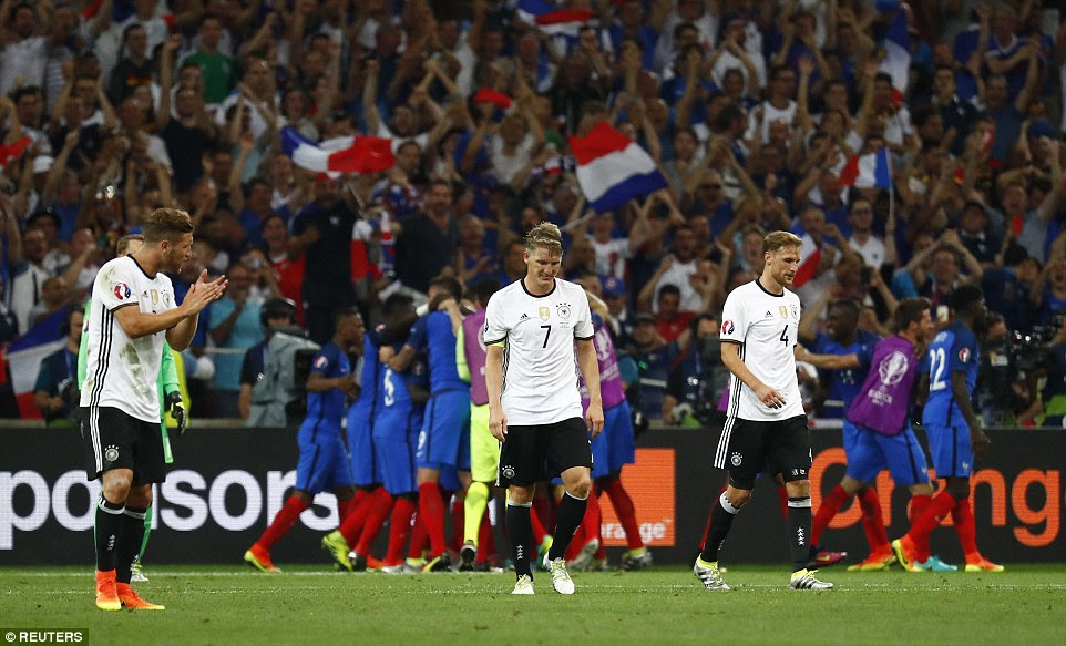 Germany's players look crestfallen as the French celebrate behind them in front of flying Tricolours as the host nation progressed