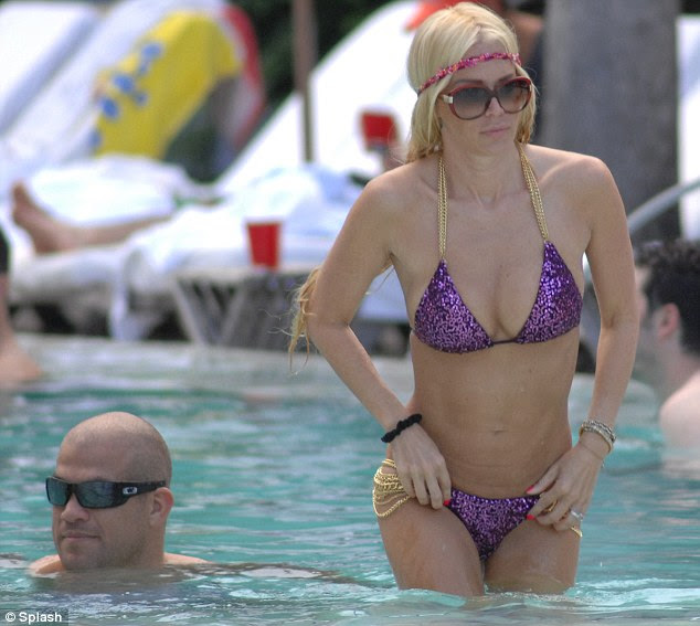 Poolside fashion: Jameson accessorised her bikini with a pink headband, gold bracelets and oversized brown sunglasses