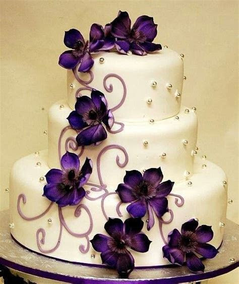 White 3 tier wedding cake with purple flowers and silver