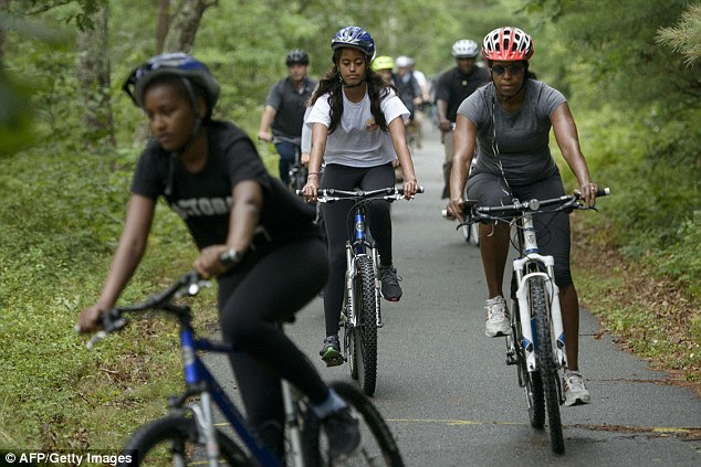 Surrounded: The Obama family was surrounded by Secret Service agents while biking. Sasha Obama (far left) led her sister, Malia (center), and mother Michelle (far right)