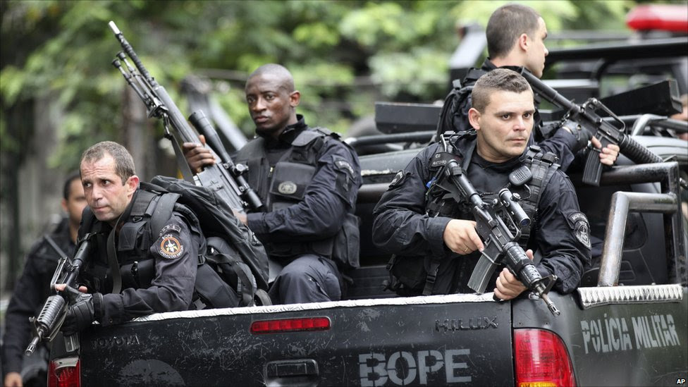 Police officers ride on a vehicle after a police operation at the Vila Cruzeiro slum in Rio de Janeiro, Brazil.