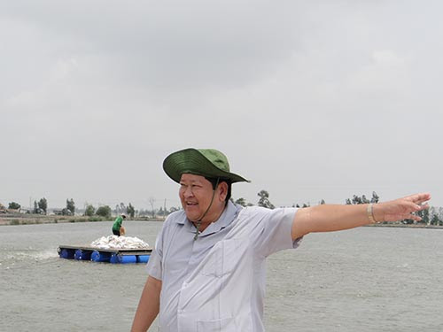 Ông Năm Hùng bên hồ nuôi cá của mình