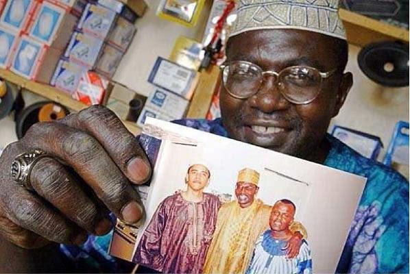 Malik Obama displays a 1980s-era photograph of Barack Obama in Kenya, wearing African garb