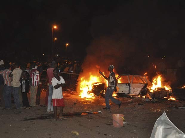 Pessoas se reúnem na área em que uma bomba explodiu em Abuja, capital da Nigéria, nesta quinta (1º) (Foto: AP Photo/Gbemiga Olamikan)