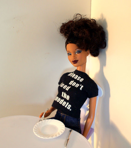 """Barbie doll wearing a shirt that says """"please don't feed the models"""" seated at a table with an empty plate in front of her."""
