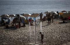Menino se refresca em chuveiro  na praia do Arpoador, no Rio de Janeiro. 30/01/2014 REUTERS/Ricardo Moraes