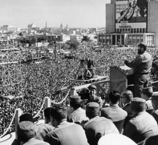 Fidel discursando em praça pública e sendo acompanhado por multidão