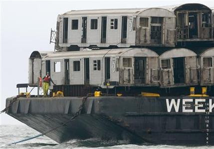 A worker on a barge stands near retired New York City subway carriages before they are dropped into the Atlantic Ocean to create an artificial reef near the coast Of Ocean City, Maryland, May 16, 2008. REUTERS-Tim Shaffer