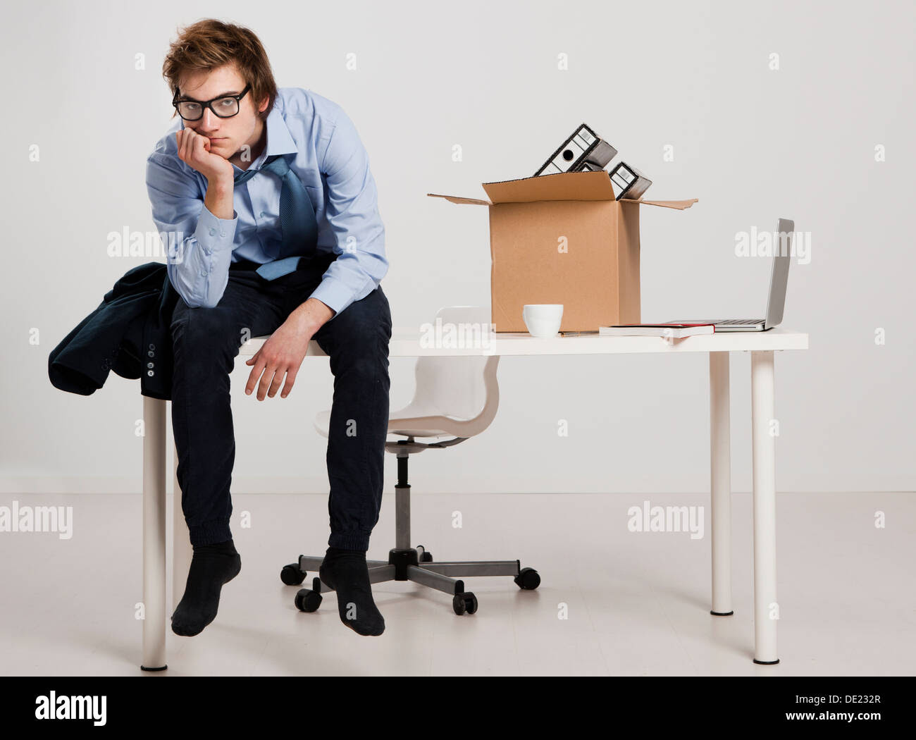 Young man sitting on the desk after being fired Stock Photo ...