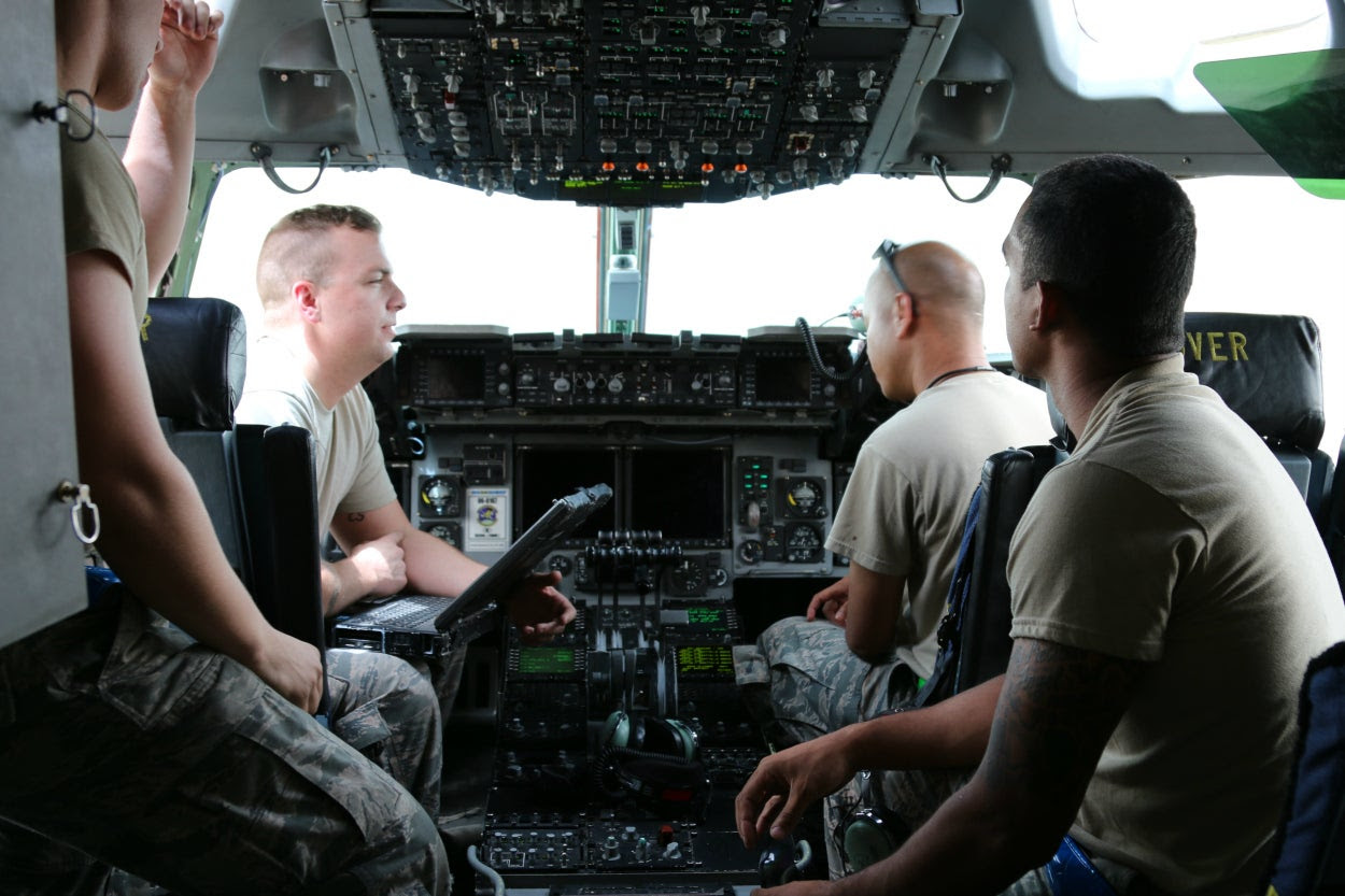 U.S. Air Force personnel perform ground checks in the cockpit of a C-17 cargo plane at an undisclosed location in the Persian Gulf region.