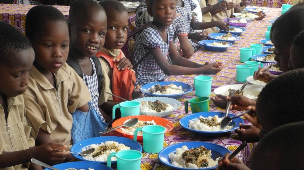 Un grupo de escolares come arroz en el centro educativo de N'Zikro, en Costa de Marfil.