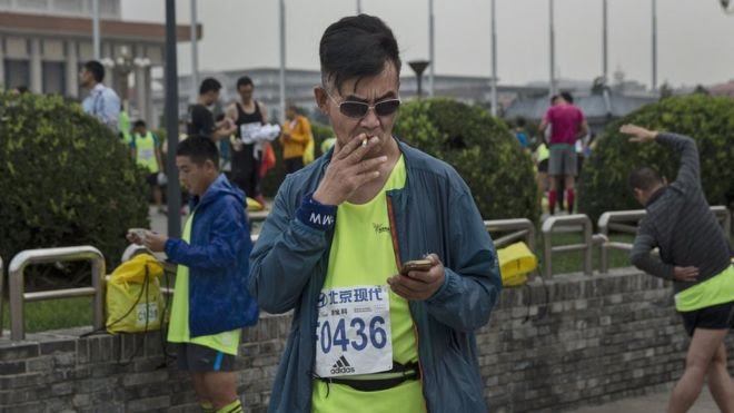 A participant smokes a cigarette before competing in the 2015 Beijing Marathon on 20 September