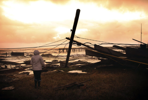 Kim Johnson looks over the destruction near her seaside apartment in Atlantic City, N.J., Tuesday, Oct. 30, 2012. Sandy, the storm that made landfall Monday, caused multiple fatalities, halted mass transit and cut power to more than 6 million homes and businesses. (AP Photo/Seth Wenig)