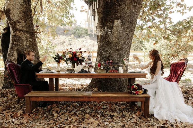 eine Rustikale tablescape mit Burgund samt Stühle mitten im Wald