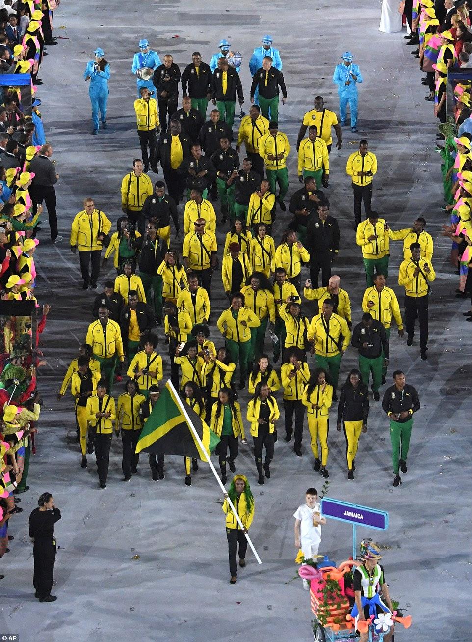 Equipe Jamaica, vestindo amarelo, preto e verde, foram conduzidos por Shelly-Ann Fraser-Pryce, que carregou a bandeira do seu país