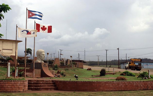 In this June 22, 2011 photo, a Canadian flag flies alongside the Cuban flag at the entrance of Pedro Sotto Alba nickel processing plant in Moa, Holguin province, Cuba. A Cuban court has convicted a dozen people of corruption, including high-ranking government officials, an executive at a state-run nickel company and workers from a project operating under a Cuban-Canadian joint concern, official media announced Tuesday, Aug. 21, 2012. (AP Photo/Ismael Francisco, Cubadebate)