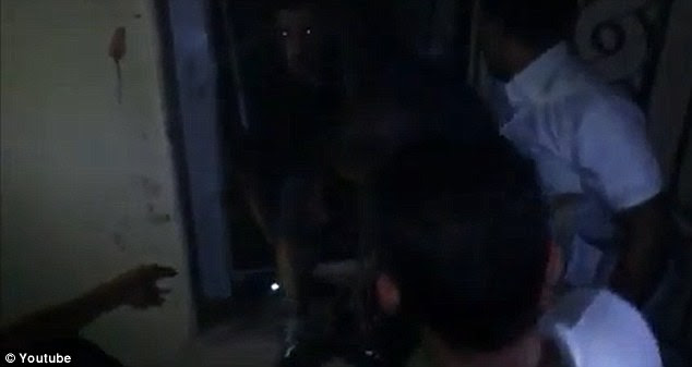 Desperate: Stevens' legs can be seen emerging from the doorway as Libyans are apparently trying to help him