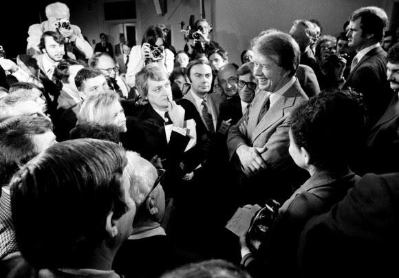 El presidente Carter, a la derecha, es rodeado por periodistas en Washington después de una conferencia de prensa en la que anunció la eliminación de la prohibición de viajar a Cuba, Vietnam, Corea del Norte y Camboya. Carter trató de normalizar las relaciones con Cuba poco después de tomar posesión en 1977. Foto de AP, Archivo de The Washington Post.