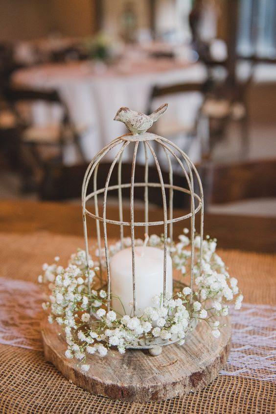 eine kleine vintage Käfig mit einem Vogel auf der Spitze, platziert auf einem hölzernen Scheibe, eine Kerze und baby Atem