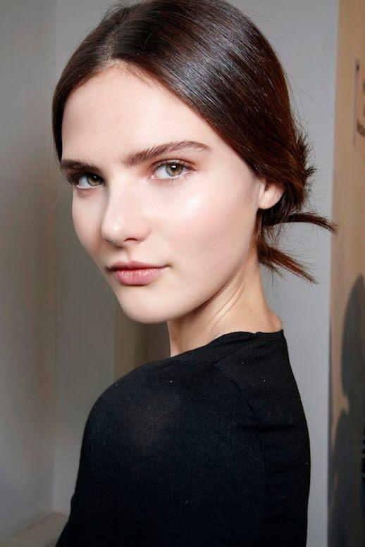 Le Fashion Blog Beauty Dewy Skin Thick Eyebrows Low Bun Black Long Sleeve Top Via The Zoe Report