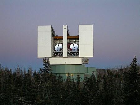 large binocular telescope with doors open, showing dual telescopes inside.
