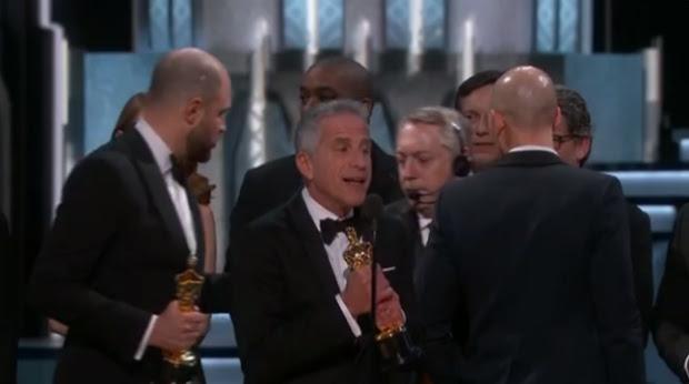 Um produtor do Oscar, com microfone na cabeça, entra no palco e avisa que houve um erro